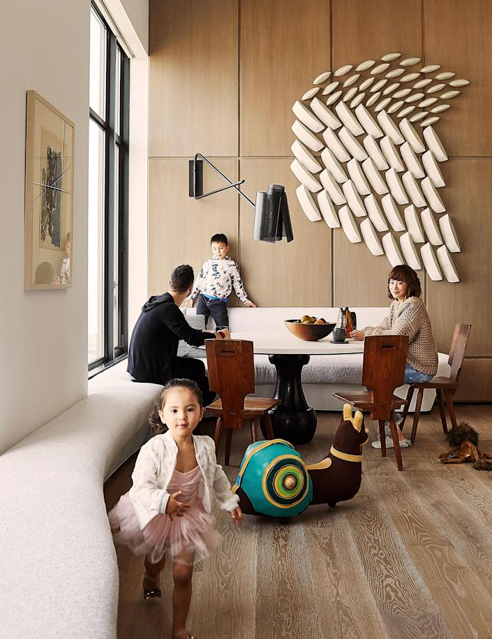 The family sits at a table by Michel Amar; vintage chairs by Pierre Chapo. Custom Banquette in a Holly Hunt performance fabric; Pierre Yovanovitch wall lamp; Artwork by Maren Kloppmann.