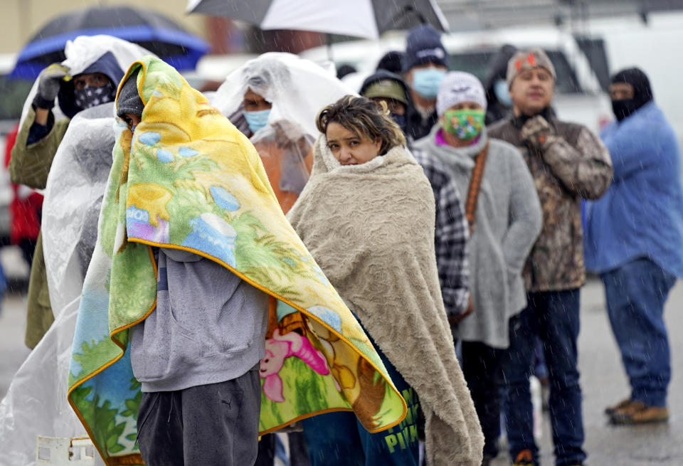 People wait in line to fill propane tanks on Wednesday in Houston.