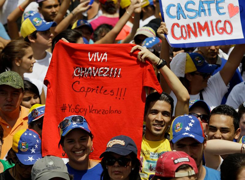 "In this April 7, 2013 photo, a man holds up a T-shirt that reads in Spanish ""Long live Chavez!"" with the name Chavez replaced with Capriles, referring to opposition presidential candidate Henrique Capriles, at a campaign campaign rally in Valencia, Venezuela. A dozen voters interviewed across the country repeated the same explanation for their first opposition vote: anger at food shortages, electrical blackouts, government corruption and inefficiency and a personal dislike for the ruling party candidate Nicolas Maduro, a former foreign minister who talks constantly about Chavez but doesn't share his mentor's charisma, talent for public speaking or long list of projects and proposals for improving Venezuela. Another factor was dissatisfaction over the luxurious lifestyles of high-ranking government officials who drive high-end cars and live in upscale neighborhoods, despite their purported socialist ideas. (AP Photo/Fernando Llano)"