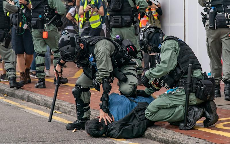 A pro-democracy supporter is detained by riot police during an anti-government rally in Hong Kong - Getty