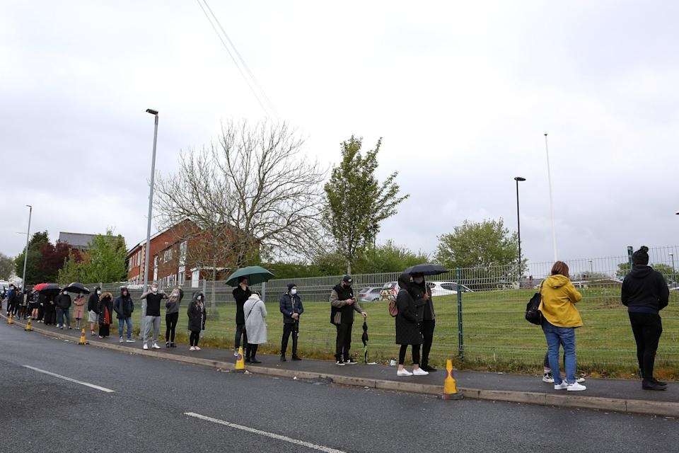 People are seen queueing to get vaccinated at Essa Academy on May 15, 2021 in Bolton, EnglandGetty Images