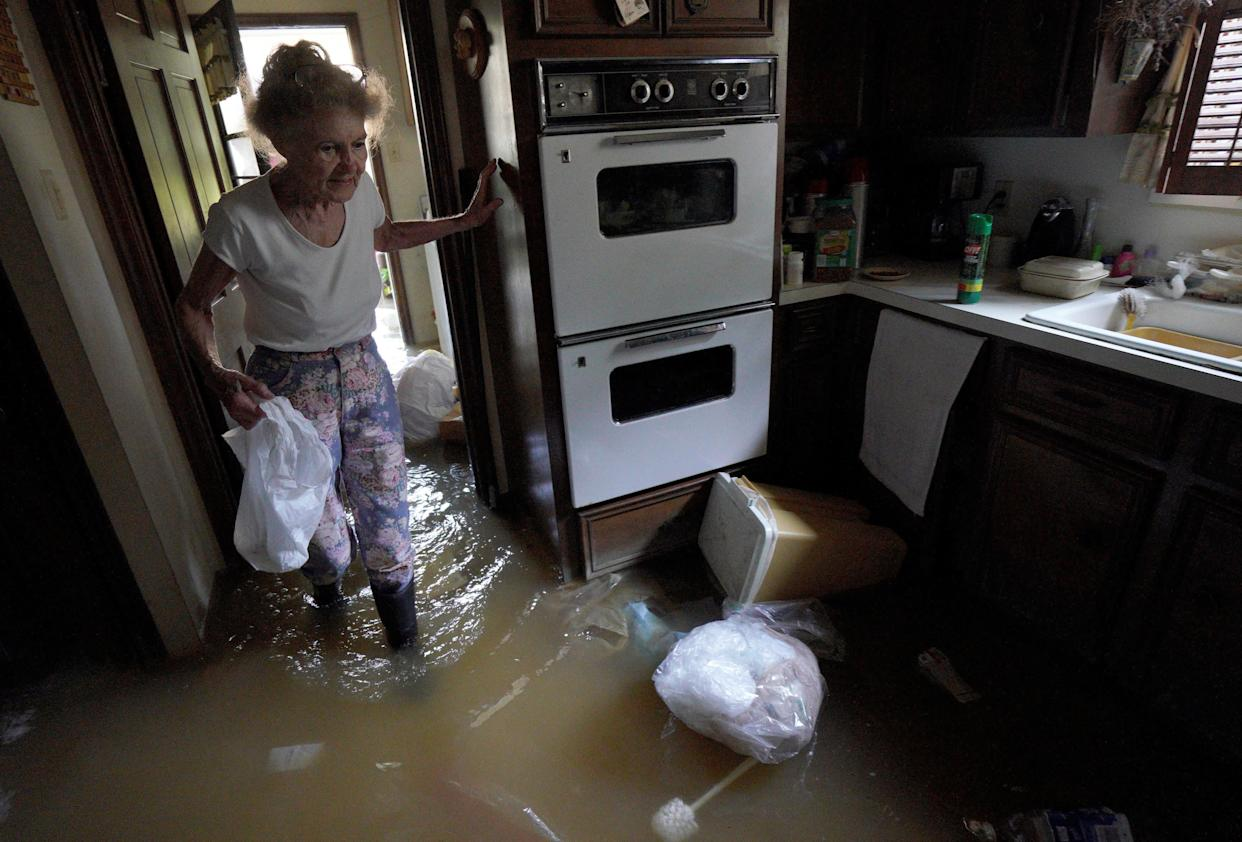 Nancy McBride collects items from her flooded kitchen as she returns to her home on Sept. 1 after the record-breaking rainfall in Houston.