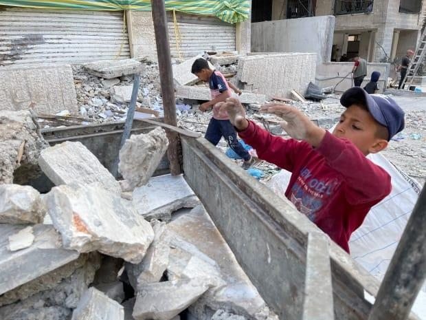 A boy helps load rubble into a donkey cart on a residential street in central Gaza.