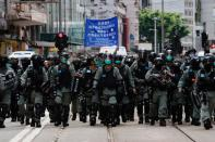 Riot police officers walk as anti-national security law protesters march during the anniversary of Hong Kong's handover to China from Britain, in Hong Kong