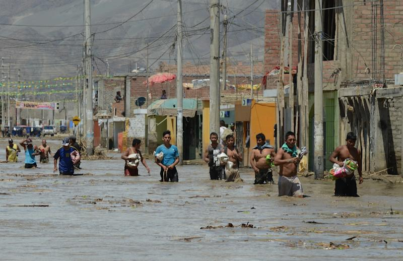 Residents of the town of Huarmey, 300 km north of Lima, wade through muddy water in the street after a flash flood hit the area the night before (AFP Photo/Cris Bouroncle)