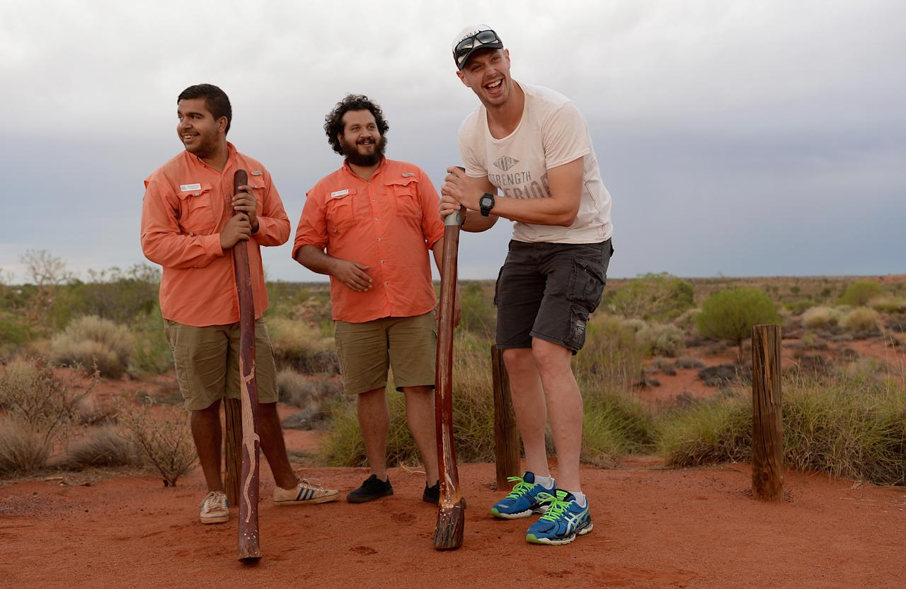 AYERS ROCK, AUSTRALIA - NOVEMBER 26:  Boyd Rankin of England tries his hand at playing a didgeridoo during a team visit to Uluru, which is also known as Ayers Rock, on November 26, 2013 in Ayers Rock, Australia.  (Photo by Gareth Copley/Getty Images)
