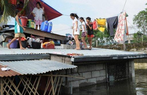 A family gathers on the roof of their home in Calumpit town, north of Manila. Philippine authorities have scrambled to provide food and other emergency provisions to more than two million people affected by widespread flooding, as the death toll rose to 66