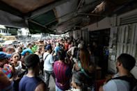 People queue to buy food in the Petare neighborhood of Caracas -- some say their food stocks are going bad due to a lack of electricity
