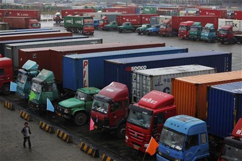 A man walks near trucks parked in a shipping container area at Shanghai Yangshan port