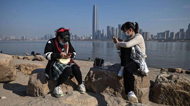 PHOTO: Women wearing face masks look at their mobile phones on the banks of the Yangtze River in Wuhan, China's central Hubei province on January 19, 2021.  (Hector Retamal/AFP via Getty Images)