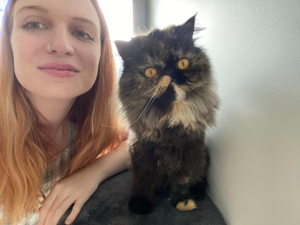 Madolline Gourley smiling for the camera in a selfie with a cat.