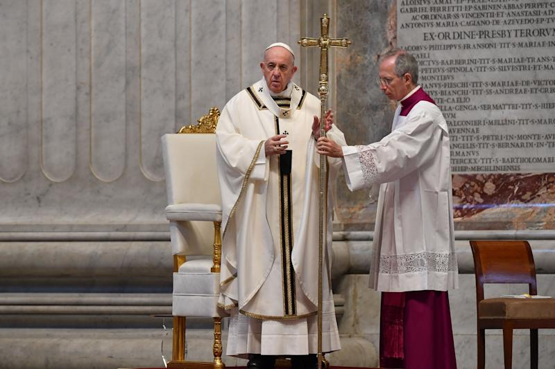 Pope Francis is assisted by Master of Pontifical Liturgical Ceremonies, Italian priest Guido Marini (R) as he celebrates Easter Sunday Mass on April 12, 2020 behind closed doors at St. Peter's Basilica in The Vatican, during the lockdown aimed at curbing the spread of the COVID-19 infection, caused by the novel coronavirus. (Photo by Andreas SOLARO / POOL / AFP) (Photo by ANDREAS SOLARO/POOL/AFP via Getty Images)