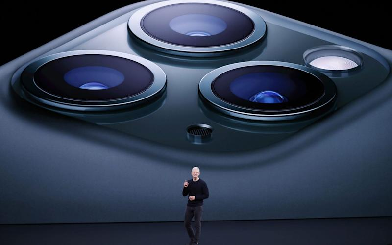Tim Cook stands before the iPhone 11 Pro, Apple's latest phone - REX