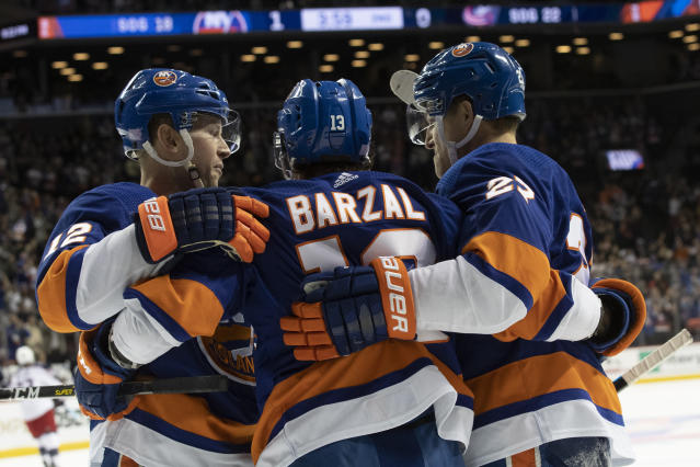 New York Islanders center Mathew Barzal (13) celebrates after scoring a goal with centers Josh Bailey (12) and Anders Lee (27) during the second period of an NHL hockey game against the Columbus Blue Jackets, Saturday, Nov. 30, 2019, in New York. (AP Photo/Mary Altaffer)