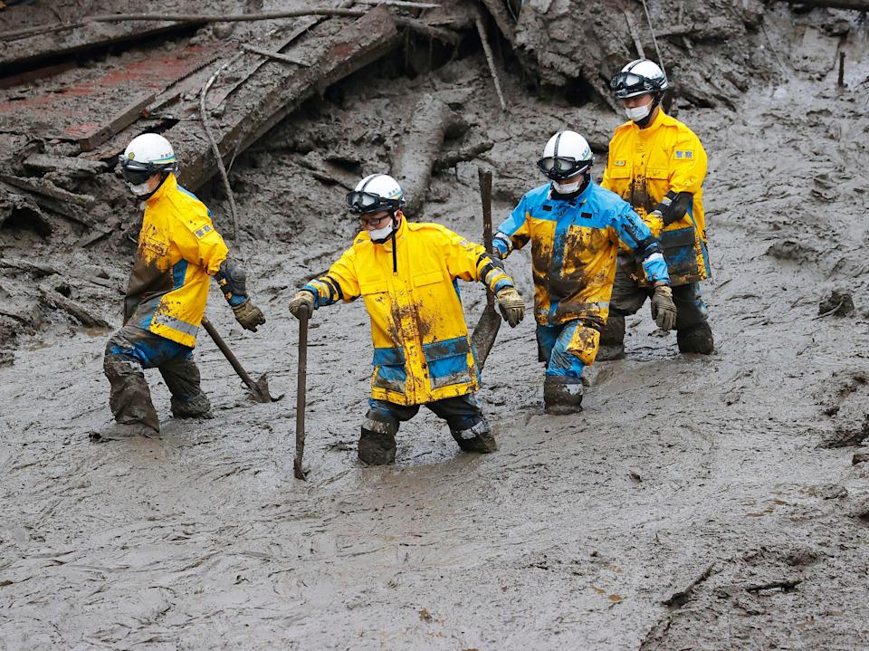 Rescuers wade through the mud in Atami, southwest of Tokyo (AP)