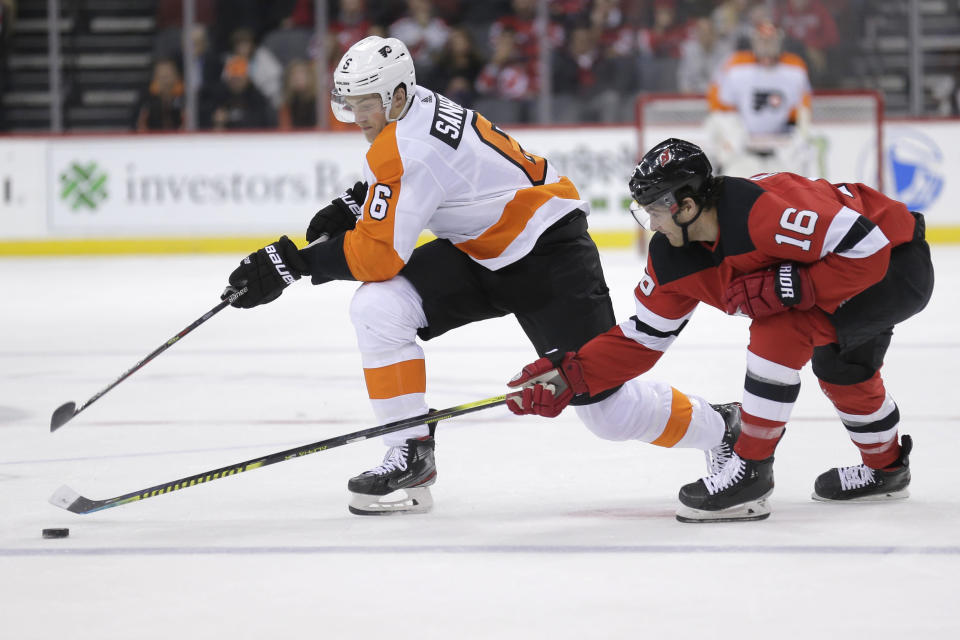 Philadelphia Flyers' Travis Sanheim, left, and New Jersey Devils' Kevin Rooney compete for the puck during the first period of an NHL hockey game in Newark, N.J., Friday, Nov. 1, 2019. (AP Photo/Seth Wenig)