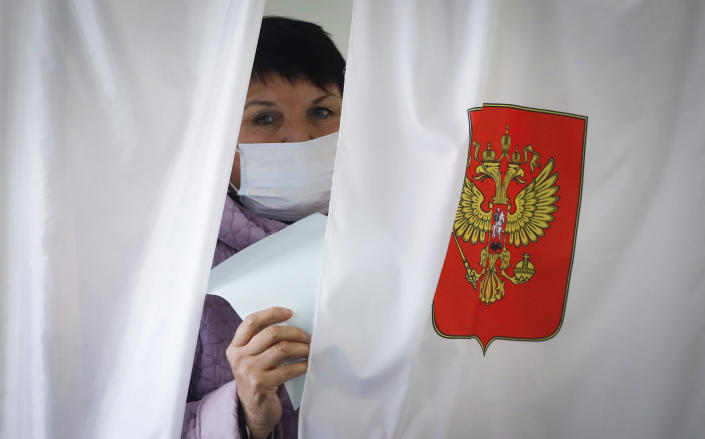 A woman wearing a face mask to protect against coronavirus infection leaves a voting booth at a poling station during Leningrad region's governor and municipal elections in Luppolovo village, outside St. Petersburg, Russia, Sunday, Sept. 13, 2020. Leningrad region is the territory surrounding St. Petersburg. Elections are being held to choose governors and legislators in about half of Russia's regions. (AP Photo/Dmitri Lovetsky)