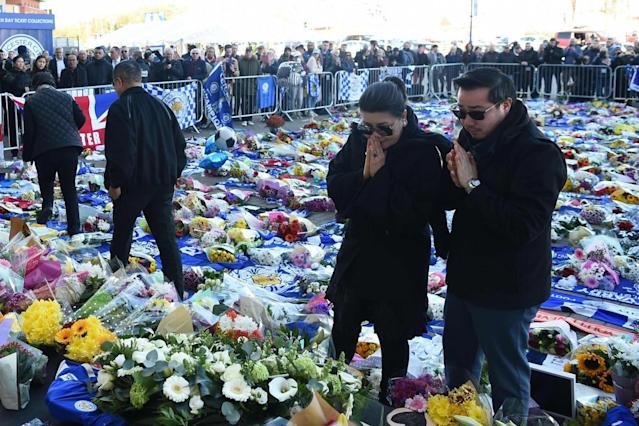 Aiyawatt Srivaddhanaprabha (R) and Aimon Srivaddhanaprabha (L) view flowers and tributes left (AFP/Getty Images)