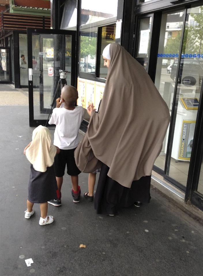In this photo dated Tuesday, July 23, 2013, a veiled woman walks with her children in Trappes, southwest of Paris. Police clashed last week in Trappes with crowds protesting the arrest of a man who allegedly attacked a police officer after his wife, a convert to Islam like him, was ticketed for veiling her face in public.(AP Photo/Elaine Ganley)