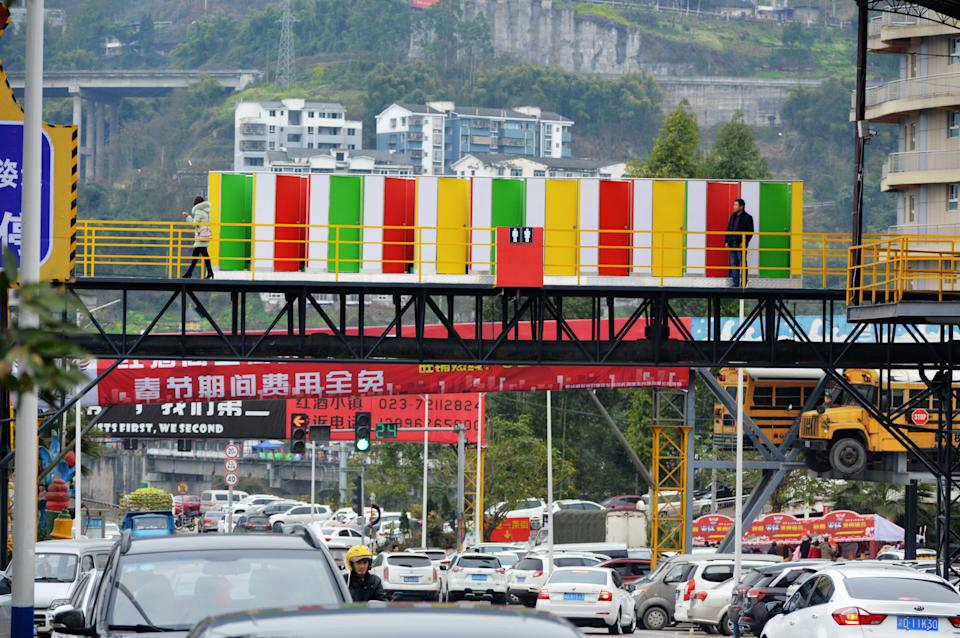 A view of the toilet built on a footbridge across a road in southwest China's Chongqing Municipality Friday Feb. 23, 2018. The 11 colorful toilet closets are placed there to ease the shortage of toilets around a tourism attraction. (Photo credit: Feature China / Barcroft Media via Getty Images)