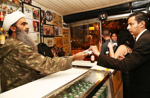 SAO PAULO, BRAZIL - APRIL 29: Osama bin Laden lookalike Ceara Francisco Helder Braga Fernandes (L) serves a customer in his 'Bar do Bin Laden' on April 29, 2014 in Sao Paulo, Brazil. Braga says he was known as the 'Beard Man' before 9/11 but became known as a Bin Laden lookalike following the 9/11 attacks. He says he is Christian and continues to play the role to support his business. (Photo by Mario Tama/Getty Images)