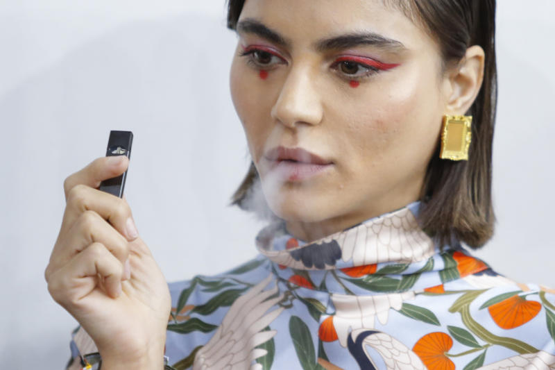 A model smokes a vape before the Snow Xue Gao Spring Summer 2018 show during New York Fashion Week on September 8, 2017 in New York. / AFP PHOTO / EDUARDO MUNOZ ALVAREZ (Photo credit should read EDUARDO MUNOZ ALVAREZ/AFP/Getty Images)