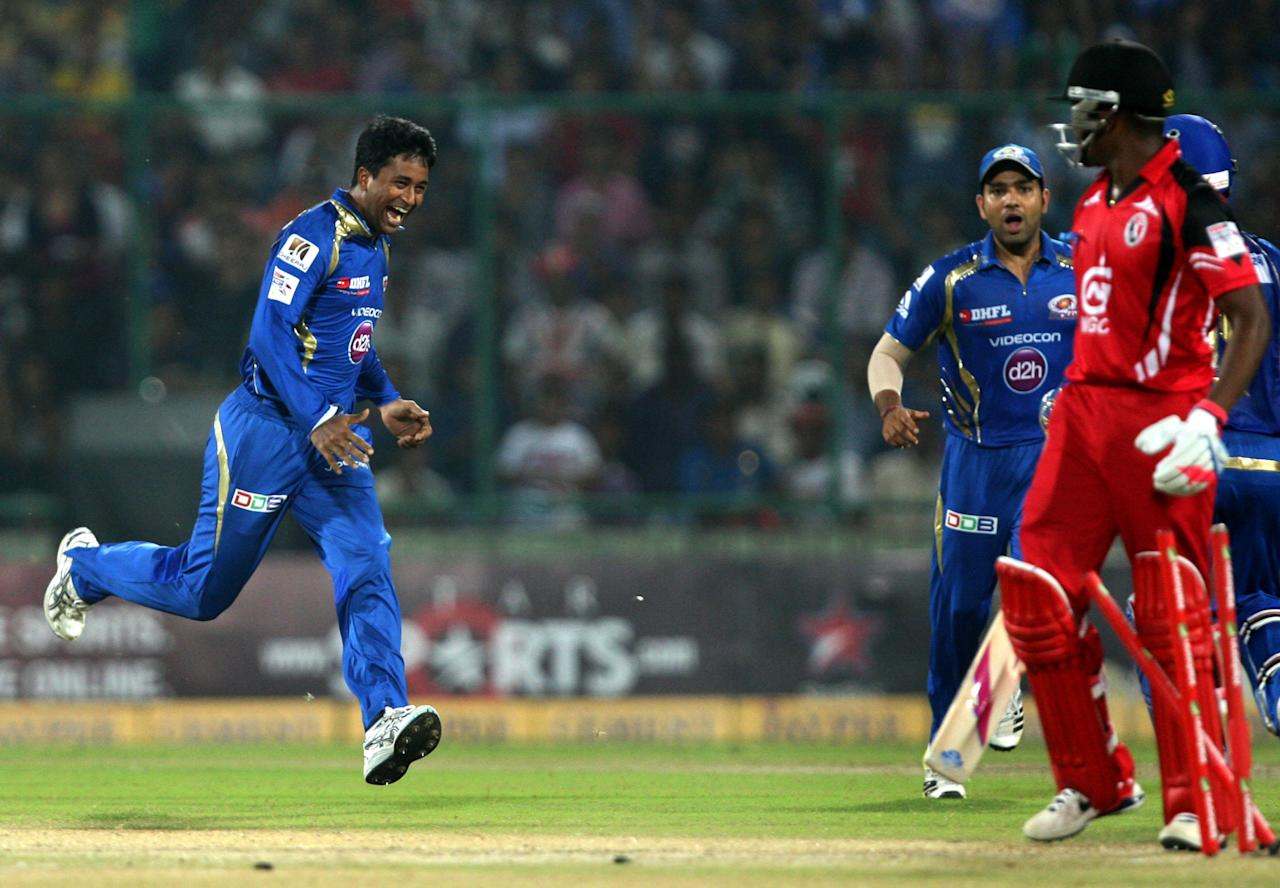 MI bowler Pragyan Ojha and captain Rohit Sharma celebrates fall of wicket during the 2nd CLT20 semi-final match between Mumbai Indians and Trinidad & Tobago at Feroz Shah Kotla, Delhi on Oct. 5, 2013. (Photo: IANS)
