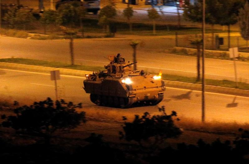 Turkish soldiers on an infantry fighting vehicle (IFV) drive near the Turkish-Syrian border in Ceylanpinar