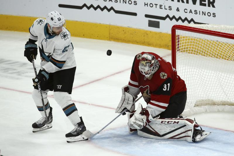 Arizona Coyotes goaltender Adin Hill (31) makes a save on a shot as San Jose Sharks right wing Barclay Goodrow (23) looks on during the second period of an NHL hockey game Tuesday, Jan. 14, 2020, in Glendale, Ariz. (AP Photo/Ross D. Franklin)
