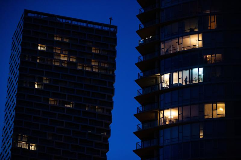 A man stands in the window of an upper floor condo as people have been urged to stay home to help prevent the spread of the coronavirus in Vancouver on March 24, 2020. (Photo: Darryl Dyck/CP)