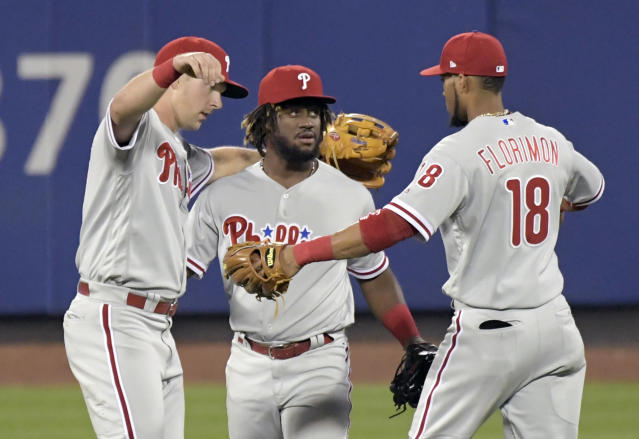 Philadelphia Phillies' Rhys Hoskins, left, Odubel Herrera and Pedro Florimon (18) celebrate after they defeated the New York Mets in a baseball game Friday, Sept. 7, 2018 in New York. (AP Photo/Bill Kostroun)