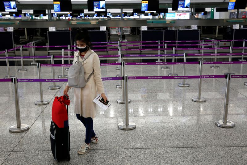 FILE PHOTO: A passenger wearing a protective face mask waits for check in, following the outbreak of the new coronavirus (COVID-19), at Hong Kong International Airport