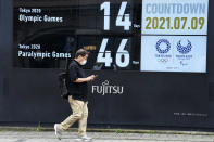 A man wearing a face mask walks past the countdown clock for the Tokyo 2020 Olympic and Paralympic Games near the Shimbashi station, Friday, July 9, 2021, in Tokyo. (AP Photo/Eugene Hoshiko)