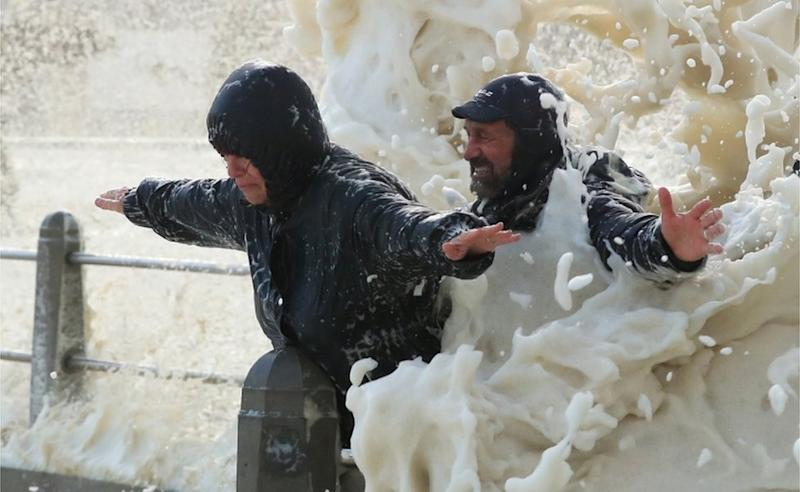 A man and a woman dressed in anoraks throw their arms out as the water hits their backs - one grimaces, the other smiles.