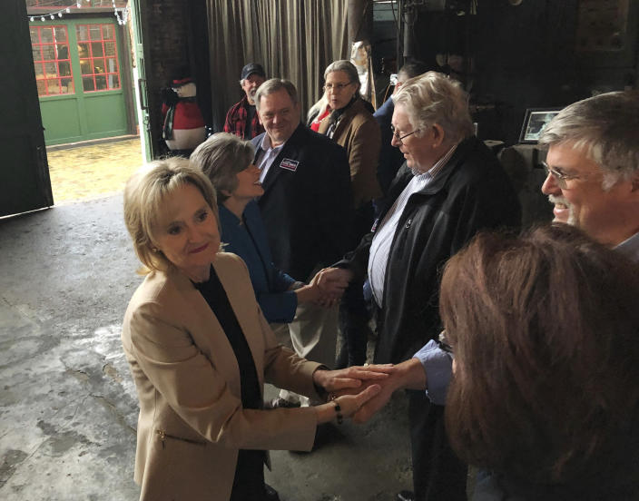 Sen. Cindy-Hyde Smith, left, R-Miss., and Sen. Joni Ernst, R-Iowa, greet supporters attending a Hyde-Smith campaign event Sunday, Nov. 25, 2018, at the Mississippi Industrial Heritage Museum in Meridian, Miss. Hyde-Smith, appointed by Mississippi Gov. Phil Bryant, faces Democrat Mike Espy in a runoff election Tuesday for the remaining two years of a Senate term begun by Thad Cochran before he retired. (AP Photo/Jeff Amy)