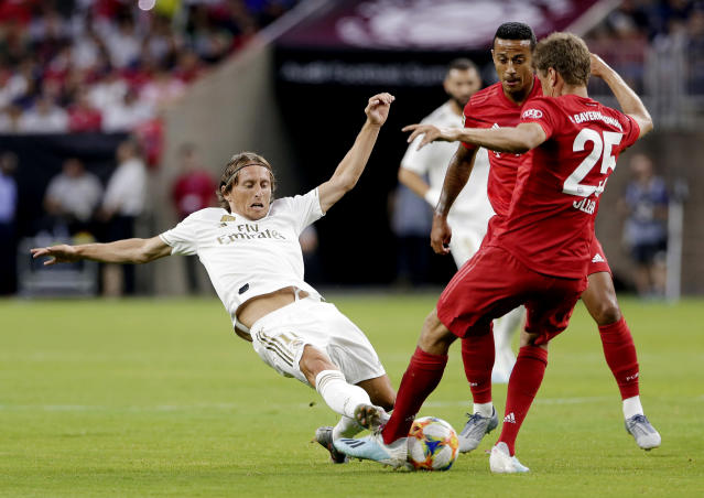 Real Madrid forward Gareth Bale, left, slides as he goes for the ball against FC Bayern's Thiago Alcntara, center, and Thomas Muller (25) during the first half of an International Champions Cup soccer match Saturday, July 20, 2019, in Houston. (AP Photo/Michael Wyke)