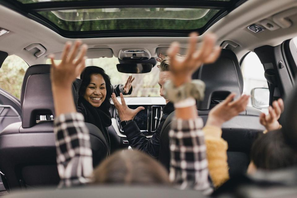 An image of a family raising their hands while on a road trip.