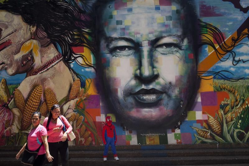 A boy dressed in a Spiderman costume poses for a photo next to a mural of Venezuela's late President Hugo Chavez painted on a wall of the Museo de Bellas Artes in Caracas, Venezuela, Tuesday, March 4, 2014. He's been dead a year, but Chavez's face and voice are everywhere. He bangs out the national anthem on state radio every morning and the national guard has even blasted his voice reciting poetry to drive rock-throwing protesters off the street. (AP Photo/Rodrigo Abd)