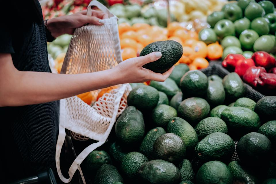 Cropped shot of young Asian woman shopping for fresh organic avocados in supermarket. She is shopping with a cotton mesh eco bag and carries a variety of fruits and vegetables. Zero waste concept