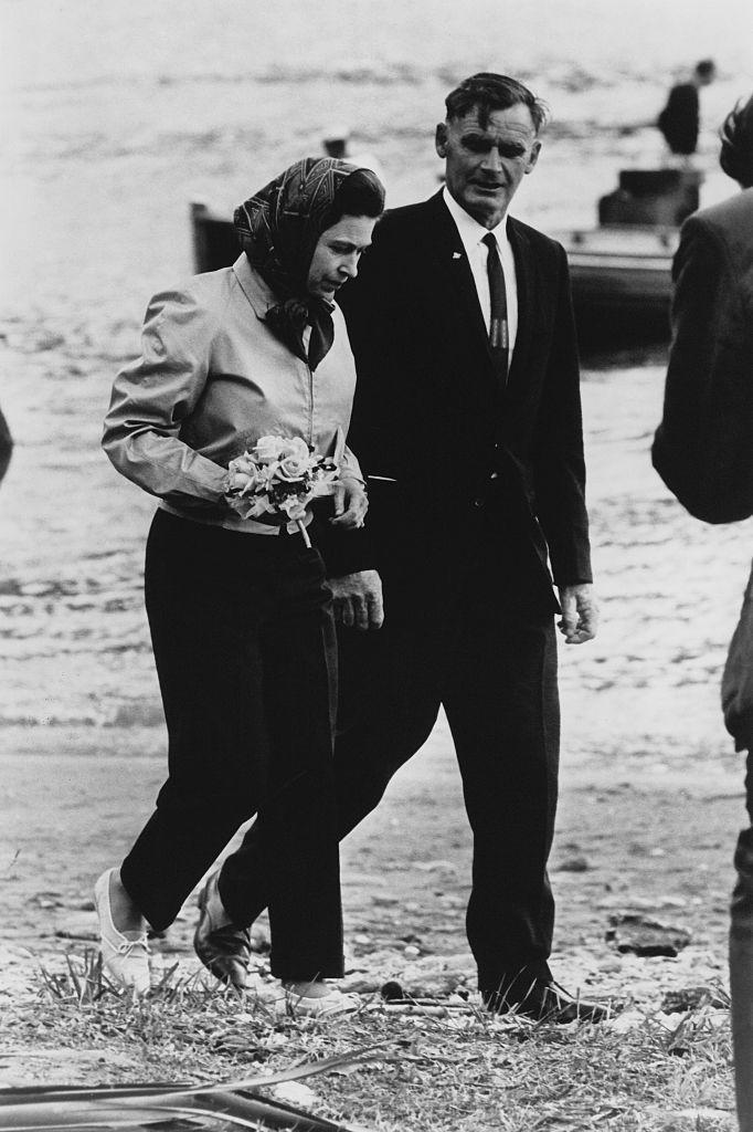 """<p>Queen Elizabeth is seen disembarking<a href=""""https://www.townandcountrymag.com/society/tradition/a23456210/royal-yacht-britannia-history/"""" rel=""""nofollow noopener"""" target=""""_blank"""" data-ylk=""""slk:from Britannia, the royal yacht"""" class=""""link rapid-noclick-resp""""> from Britannia, the royal yacht</a>, during her royal tour of New Zealand. The monarch chose to wear her signature head scarf and casual white shoes to walk across the Ship Cove beach. <br></p>"""