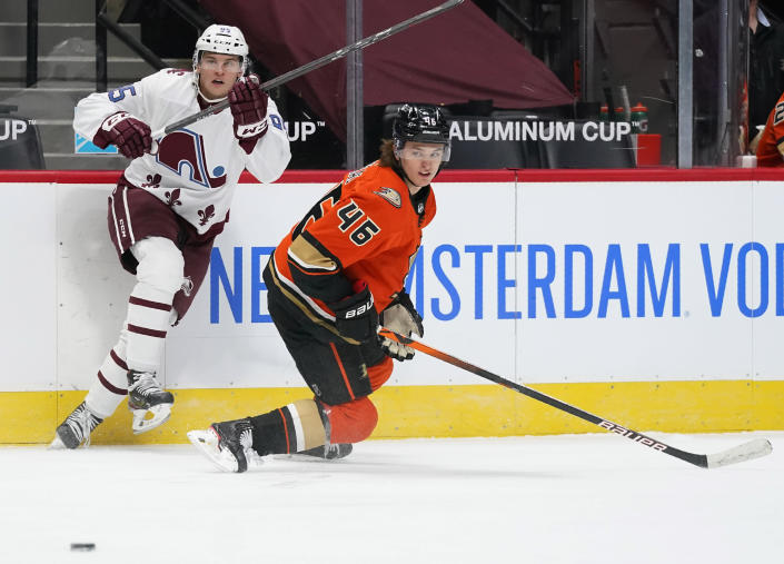 Colorado Avalanche left wing Andre Burakovsky, left, pursues the puck with Anaheim Ducks center Trevor Zegras in the first period of an NHL hockey game Friday, March 5, 2021, in Denver. (AP Photo/David Zalubowski)