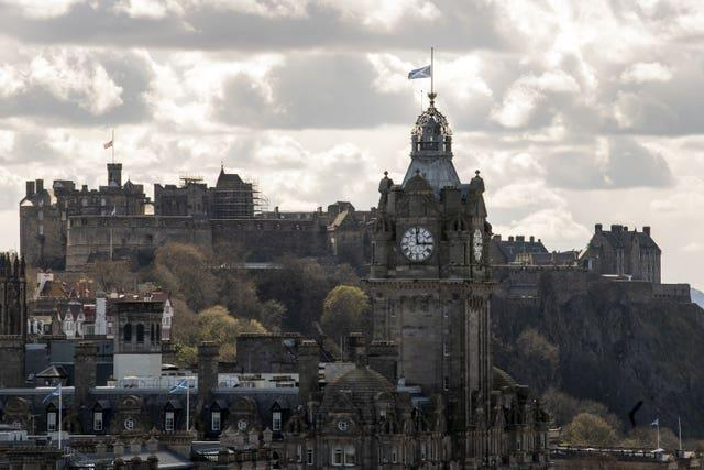 The Union flag above Edinburgh Castle (left) and the flag of Scotland on the Balmoral clock in Edinburgh flying at half mast (Lesley Martin/PA)