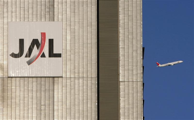 File picture showing a JAL aircraft flying near a JAL building at Tokyo's Haneda Airport