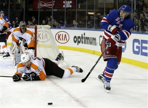 New York Rangers left wing Carl Hagelin (62) passes in front of Philadelphia Flyers defenseman Luke Schenn (22) and Flyers goalie Ilya Bryzgalov (30), from Russian, during the second period of their NHL hockey game at Madison Square Garden in New York, Tuesday, Jan. 29, 2013. (AP Photo/Kathy Willens)
