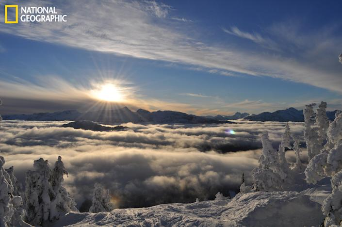 """""""This picture was taken at Mt. Washington, Vancouver Island, British Columbia. It was 3:30 p.m., December 2011. I had a great day skiing and was on my last run. I stayed on top for as long as I could (before the patrollers do their sweep) so I could take some pictures. It was a magical time as I watched the sun slowly dip down below the clouds. This was one of many pictures I took that afternoon. I thought of how many people in the Comox Valley were missing this wonderful scene. I love skiing, boarding and shooting."""" (Photograph Courtesy Amy Nygren /National Geographic Your Shot)"""