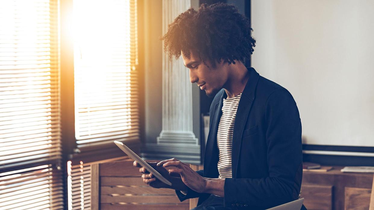 Side view of young handsome African man using his digital tablet while sitting on table at his working place.