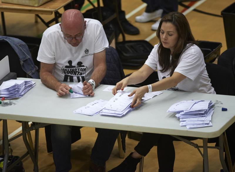Counting staff sort through ballots at a counting centre in Islington, London, on June 8, 2017, after the polls closed in Britain's general election. Prime Minister Theresa May is poised to win Britain's snap election but lose her parliamentary majority, a shock exit poll suggested on June 8, in what would be a major blow for her leadership as Brexit talks loom. The Conservatives were set to win 314 seats, followed by Labour on 266, the Scottish National Party on 34 and the Liberal Democrats on 14, the poll for the BBC, Sky and ITV showed. / AFP PHOTO / NIKLAS HALLE'N (Photo credit should read NIKLAS HALLE'N/AFP via Getty Images)