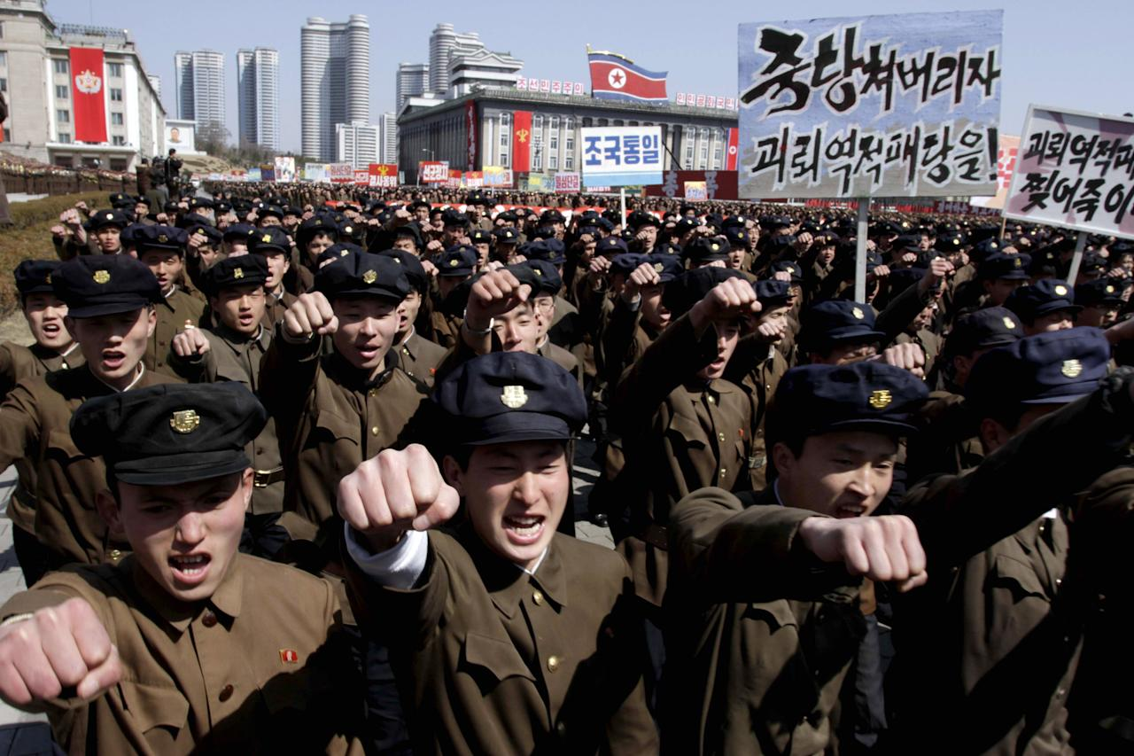 "University students punch the air as they march through Kim Il Sung Square in downtown Pyongyang, North Korea, Friday, March 29, 2013. Tens of thousands of North Koreans turned out for the mass rally at the main square in Pyongyang in support of their leader Kim Jong Un's call to arms. Placards read: ""Let's crush the puppet traitor group"" and ""Let's rip the puppet traitors to death!"" (AP Photo/Jon Chol Jin)"