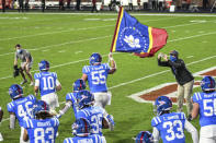 Mississippi offensive lineman Ben Brown (55) carries the Mississippi state flag onto the field for the team's NCAA college football game against South Carolina in Oxford, Miss., Saturday, Nov. 14, 2020. (AP Photo/Bruce Newman)
