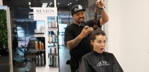 A hairdresser prepares to shave off Heather Maltman's ponytail in a salon